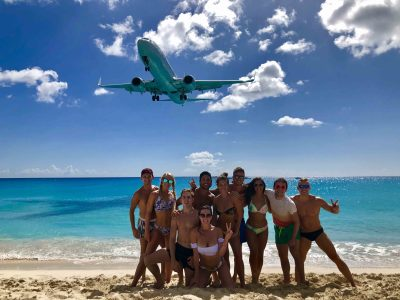 Group of Cruise artists enjoying Maho Beach while a plane lands over their head.